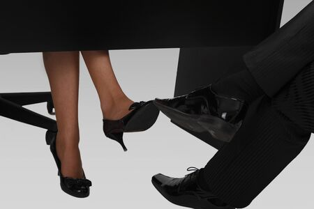 stockings feet: A womans and mans legs touching under an office desk.