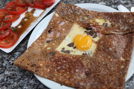 Image of a buckwheat flour pancake containing egg,ham,mushroom and cheese.Such food is specific for the entire France mostly in Normandy and Brittany.