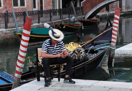 Venice,Italy,July 28th 2011: Portrait of a young gondolier using a mobile phone while waiting for clients near a venetian canal.Gondola is a major mode of touristic transport in Venice and one of the most specific icon of the city.