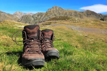 Imagen de un par de caminatas botas tirado en el césped delante de un hermoso paisaje montañoso en las montañas de los Pirineos.