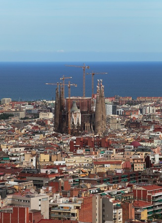 continued: Aerial view of Barcelona, Spain with the famous Sagrada Familia (Basilica and Expiatory Church of the Holy Family) in construction. The construction of the cathedral continued after the Gaudi had passed away and it develops nowadays with  an anticipated c