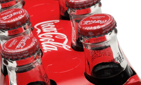 Chartres,France- October 6th, 2011: Close-up of upper part of traditional bottles of Coca Cola in a paper pack. Coca-Cola is a carbonated soft drink largely sold all over the world.