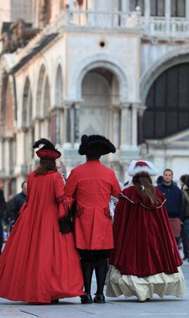 Venice,Italy - February 25th, 2011: Image of a family wearing traditional medieval costumes in San Marco Square in Venice, during The Carnival days.The Carnival of Venice (Carnevale di Venezia) is an annual festival, held in Venice, Italy and is now estab