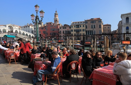 Venice,Italy- February 25th, 2011: Many tourists enjoy a traditional Italian lunch on a restaurant terrace in Venice, in the vicinity of Rialto Bridge, near the Grand Canal, the biggest waterway of the city.Venice is a special city in Italy,built in an ar