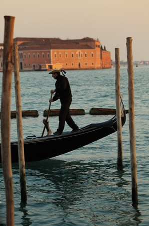 Venice,Italy- February 25th,2011: In this picture we can see through the wooden pyllons a gondolier propelling a gondola at the sunset in front of the San Giorgio Maggiore Island in Venice.