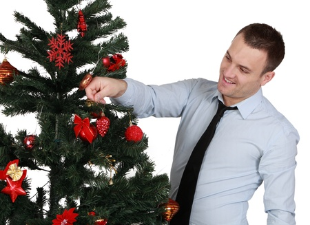 christma: A young man decorating a Christmas tree isolated against a white background.