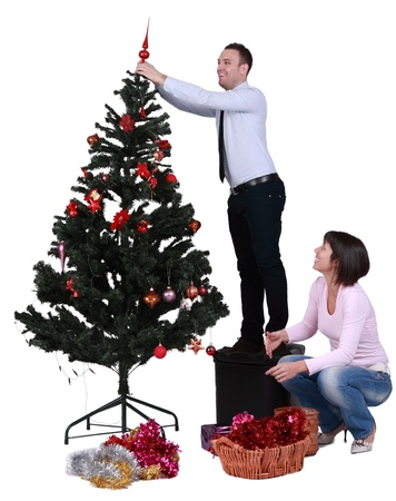 Studio shot of a young couple decorating the Christmas tree, against a white background.