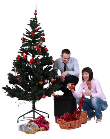 Studio shot of a young happy couple decorating the Christmas tree, against a white background. photo
