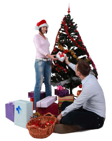 Studio shot of a young man giving a gift to his girlfriend in front of the Christmas Tree, against a white background. photo