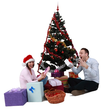 Studio shot of a young couple enjoying the gifts in front of the Christmas Tree, against a white background. photo