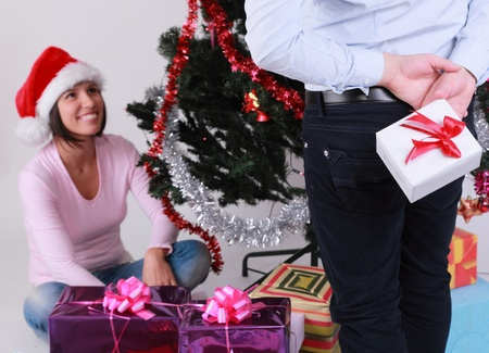 gift behind back: A man hiding gift behind his back in front of a happy young woman near the Christmas Tree.