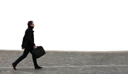 caminando: Hombre de negocios joven caminando por una calle adoquinada frente a una pared blanca. Foto de archivo