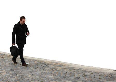 personas en la calle: Empresario caminando sobre una calle adoquinada frente a una pared blanca mientras revisa su tel�fono m�vil. Foto de archivo