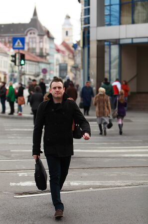 citylife: Businessman crossing the street in an old European city.