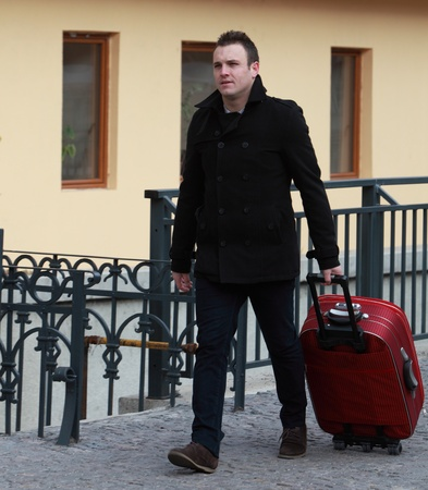 Young man with a red suitcase in a small cobbled street in a city. photo