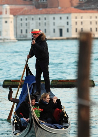 Venice,Italy,February 25th 2011: Image of a gondolier propelling his gondola with tourists in front of the San Giorgio Maggiore Island in Venice.
