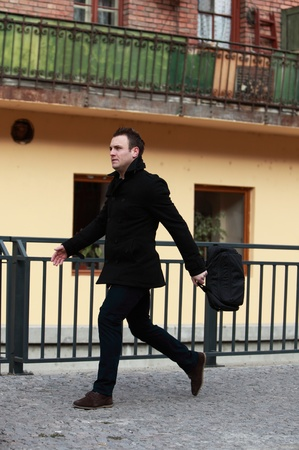 quickly: Young casual man in a hurry in a small cobbled city street.