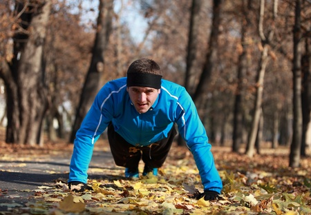 Man doing push-ups outdoor in a park in autumn.