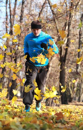 Image of a man running between falling leaves in a park in autumn. photo
