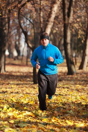 outdoor training: Man running in a forest in autumn.