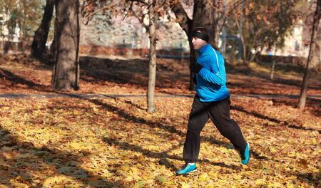 Man running in a park in autumn. photo