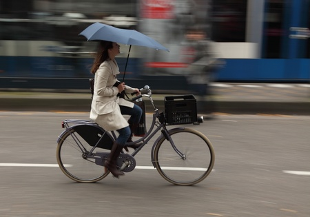 Amsterdam,The Netherlands- October 30th, 2011:Panning image of a young woman with umbrella riding her bicycle in a street in Amsterdam. Amsterdam is one of the most bicycle-friendly large cities in the world and is a centre of bicycle culture with good fa