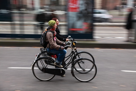 Amsterdam,The Netherlands- October 30th, 2011:Panning image of a two young women riding their bicycles in a street in Amsterdam. Amsterdam is one of the most bicycle-friendly large cities in the world and is a centre of bicycle culture with good facilitie