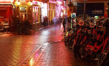 empedrado: Amsterdam, Países Bajos, 30 de octubre 2011: La imagen durante la noche de una calle adoquinada húmeda muy bien iluminado en Amsterdam.