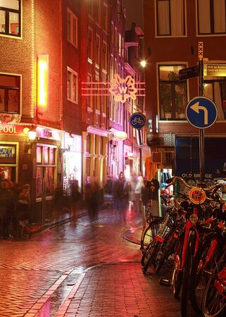 Amsterdam,Netherlands- October 30th, 2011: Verical image during the night of a wet cobbled street nicely illuminated in Amsterdam.