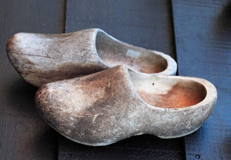 clog: Old used traditional dutch wooden clogs on a wooden surface.