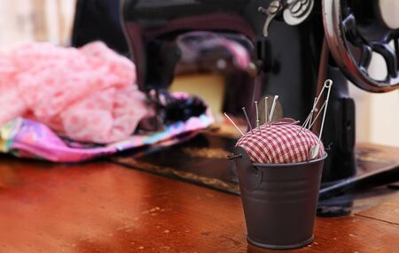 Image of an old-fashioned tailoring table.The selective focus is on the little pail with the pin-cushion. photo