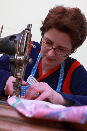Close-up of a seamstress working with an old sewing machine. photo