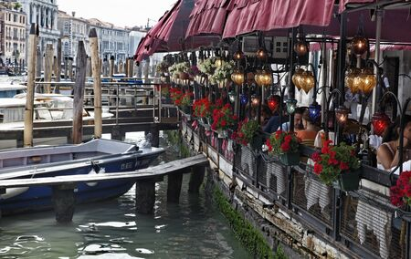 vicinity: Venice,Italy- July 28th, 2011: Many tourists enjoy a traditional Italian lunch on a restaurant terrace in Venice, in the vicinity of Rialto Bridge, near the Grand Canal, the biggest waterway of the city.Venice is a special city in Italy,built in an archip