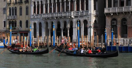Venice,Italy- July 28th, 2011: Image of three gondolas with tourists in front of traditional venetian buidlings on the Grand Canal in Venice.