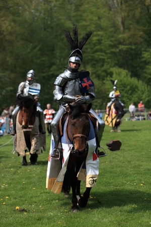 existence: Harcourt, France- April 17th, 2011:Image of three medieval knights on the battle field during a tournament held in Harcout in France, to celebrate 1100 years of existence of Normandy.