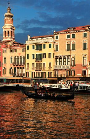 Venice, Italy- July 29th, 2011: Image of a gondola with tourists sailing at the sunset in front of a traditional building on The Grand Canal the Rialto Bridge area in Venice Italy.Venice is a special city in Italy,built in an archipelago of 117 islands fo Stock Photo - 12143465