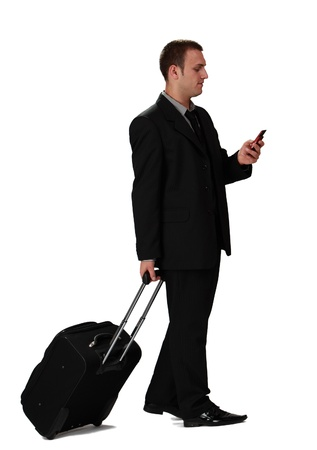 Young businessman with a suitcase reading a phone message against a white background.
