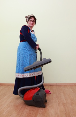 Housewife using a vacuum cleaner to clean the floor. photo