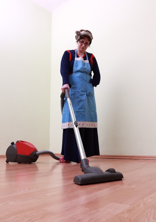 Housewife using a vacuum cleaner to clean the floor. The mai focus is on the tube of the cleaner. photo