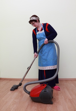 Housewife using a vacuum cleaner to clean the floor. Stock Photo - 12163913