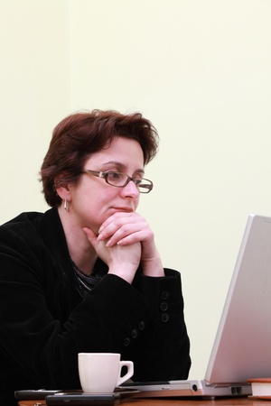 Mature businesswoman looking at her laptop on a coffe bar table. photo