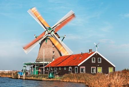 zaanse: Afbeelding van een Nederlandse molen van de Zaanse Schans, tijdens een winderige dag met motion blur op de zeilen.