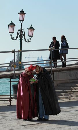 Venice,Italy- February 26th, 2011: Two tourists disguised in Venetian costumes stoped and read in a Venice travel guide on Sestiere Castello, during the carnival days.The Carnival of Venice (Carnevale di Venezia) is an annual festival, held in Venice, Ita
