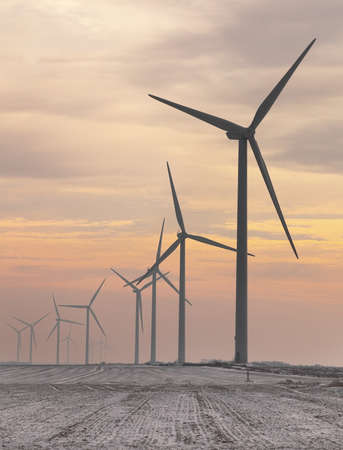 eolian: Evening image of a misty field with windturbines during the winter. Stock Photo