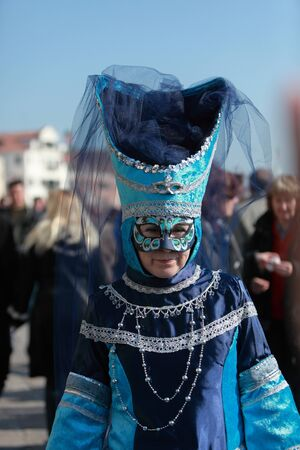 sestiere: Venice,Italy-February 26th, 2011: Image of a woman wearing a traditional blue Venetian costume and mask during the Carnival days on Sestiere Castello. The Carnival of Venice (Carnevale di Venezia) is an annual festival, held in Venice, Italy and is now es