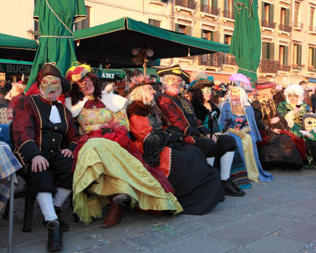 Venice,Italy-February 26th, 2011: Image of a group of disguised tourists sitting on a terrace on Sestiere Castello in Venice, during the Carnival days.The Carnival of Venice (Carnevale di Venezia) is an annual festival, held in Venice, Italy and is now es