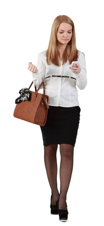 businesswoman skirt: Young woman reading a phone message while walking against a white background. Stock Photo