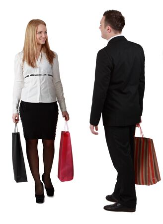 A man and a woman with shopping bags passing by themselves, against a white background. photo