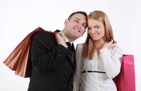 Happy couple with shopping bags against a white background  photo