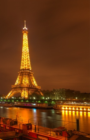 Paris,France, March 31st 2012: Night image in Paris of the illuminated Eifel Tower, river Seine and a part of a specific ship.The tower stands 324 metres tall and is the most prominent symbol of both Paris and France.
